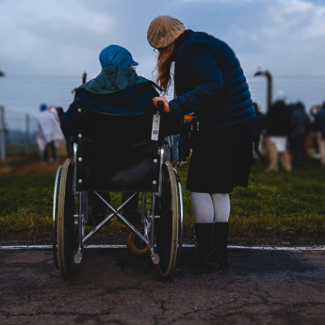 Wheelchair user and carer in a field of people